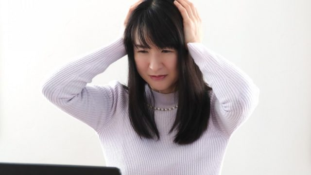 PCがウィルスに感染して頭を抱える女性